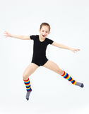 Slim teen girl doing gymnastics dance in jumping on white Stock Photos