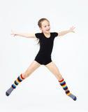 Slim teen girl doing gymnastics dance in jumping on white Stock Image