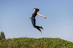 Slim teen girl dressed in jeans and a black top   jumping high over green grass against the sky. stock images