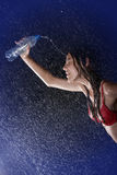 Slim teen pouring from bottle in water studio. Closeup Royalty Free Stock Image