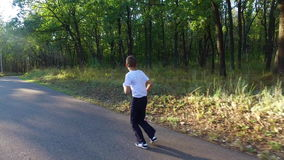 Slim teenager boy is running on paths and trails in the forest. Boy is trained good running. Sports in nature. Morning sun forest at dawn. Camera  with stock video