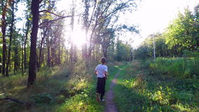 Slim teenager boy is running on paths and trails in the forest. Boy is trained good running. Sports in nature. Morning sun forest at dawn.  Camera  with stock video footage