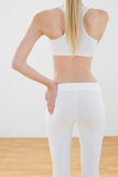 Slim tonade kvinnan som poserar i sportswear med handen på höft Royaltyfria Bilder