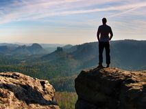 Slim tourist on the edge of rock in rock empires park  is watching over the misty and foggy morning valley to Sun Royalty Free Stock Photos