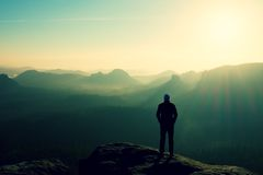 Slim tourist on the sharp peak of rock in rock empires park  is watching over the misty and foggy valley to Sun Royalty Free Stock Image