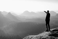 Slim tourist on the sharp peak of rock in rock empires park  is watching over the misty and foggy valley to Sun Royalty Free Stock Images