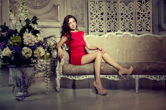 Slim trendy, luxurious, fashion woman in  lux vintage interior. Girl in red short dress on a luxury background Royalty Free Stock Photography