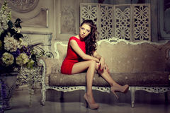 Slim trendy, luxurious, fashion woman in  lux vintage interior. Girl in red short dress on a luxury background Stock Image