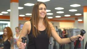Slim unrecognizable woman walks elliptical trainer isolated stock footage