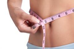 Slim Waist. Woman measures her slim waist Stock Image