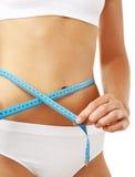 Slim waist. Slim girl measuring her body isolated on white Stock Photos