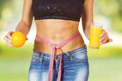 Slim Waist Slimming Body Successful Diet. Slim Waist of Young Woman with perfect healthy thin body, holding orange fruit and juice with tape measure on belly royalty free stock photography