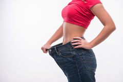 Slim waist of young woman in big jeans showing Royalty Free Stock Image