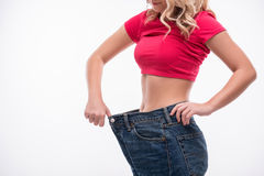 Slim waist of young woman in big jeans showing Stock Image