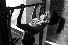 Slim well built woman holding a horizontal bar. Doing chin ups. Slim well built young woman wearing a ponytail and holding a horizontal bar while doing chin ups royalty free stock photography