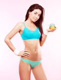 Slim woman. Beautiful slim young woman holding an orange and a measuring tape, against pink studio background Stock Images