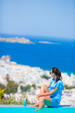 Slim woman applying sunscreen on her legs, sitting on the edge of pool background old town Mykonos in Europe Royalty Free Stock Photography