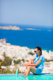 Slim woman applying sunscreen on her legs, sitting on the edge of pool background old town Mykonos in Europe Stock Photos