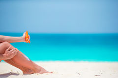 Slim woman applying sunscreen on her legs, sitting on sandy beach with sea background Stock Photo