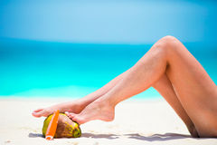 Slim woman applying sunscreen on her legs, sitting on sandy beach with sea background Royalty Free Stock Photo
