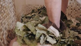 Slim woman in bath is getting steaming massage with hot oak leaves brooms, in steam-room.  stock video footage