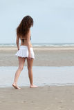Slim woman with beautiful body wearing mini skirt and bra pose at the beach Stock Images