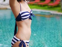 Slim woman in bikini stretching relax beside swimming pool. Blue background Royalty Free Stock Photography