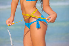 Slim woman in bikini with tape measure. For summer diet concept Royalty Free Stock Image