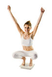 Slim woman cheering on scales Royalty Free Stock Images