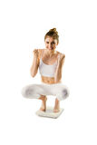 Slim woman cheering on scales Royalty Free Stock Image