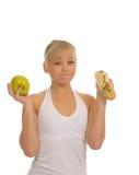 Slim woman choosing between apple and hamburger Royalty Free Stock Image