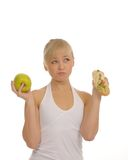 Slim woman choosing between apple and hamburger Royalty Free Stock Images