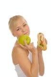 Slim woman choosing between apple and hamburger Stock Photography