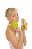 Slim woman choosing between apple and hamburger Royalty Free Stock Photography