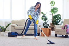 Slim woman cleaning with vacuum cleaner carpet Royalty Free Stock Images