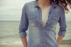 Slim woman in a denim shirt and white t-shirt stands on the beac. H against the sea in cloudy weather. She has curly hair. Her hands in her pockets. Retro colors Stock Images
