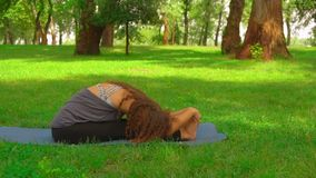Slim woman does forward bend pose in park. Caucasian woman sitting on blue yoga mat doing exercise slow motion girl with long curly hair trains outdoors. nature stock video footage