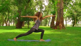 Slim woman doing asana warrior pose in park. Caucasian sportswoman practicing yoga at the open air slow motion girl with long curly hair trains outdoors. nature stock video footage