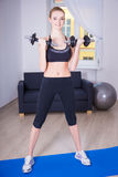 Slim woman doing exercise with dumbbells at home Stock Photography