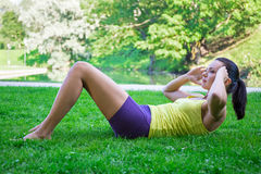 Slim woman doing exercises for abdominal muscles in park Stock Photography