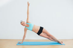 Slim woman doing the side plank yoga pose in fitness studio Royalty Free Stock Photos