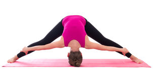 Slim woman doing stretching exercise on yoga mat isolated on whi Stock Photo
