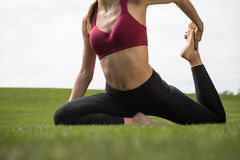 Sporty lady is exercising on lawn stock photo