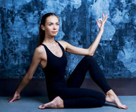 Slim woman doing yoga. Beautiful slim woman doing yoga,  against dark studio background Stock Photos