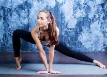 Slim woman doing yoga. Beautiful slim woman doing yoga against dark studio background Royalty Free Stock Photography