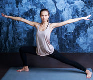 Slim woman doing yoga. Beautiful slim woman doing yoga against dark studio walls Royalty Free Stock Photo