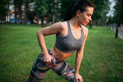 Slim woman exercise with dumbbell in summer park Stock Images