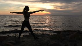 Slim woman exercising yoga warrior pose on beach. Slim fit woman exercising yoga warrior pose on the beach in glow of amazing sunset. Silhouette of fitness stock video footage
