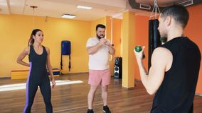 A slim woman and fat man train blows. Private coach with dumbbells. Individual weight loss drills for thick guy. Warm up stock video footage