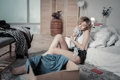 Slim woman feeling awful while packing clothes of ex boyfriend. Clothes of ex. Slim woman sitting on the floor feeling awful while packing clothes of ex stock photography
